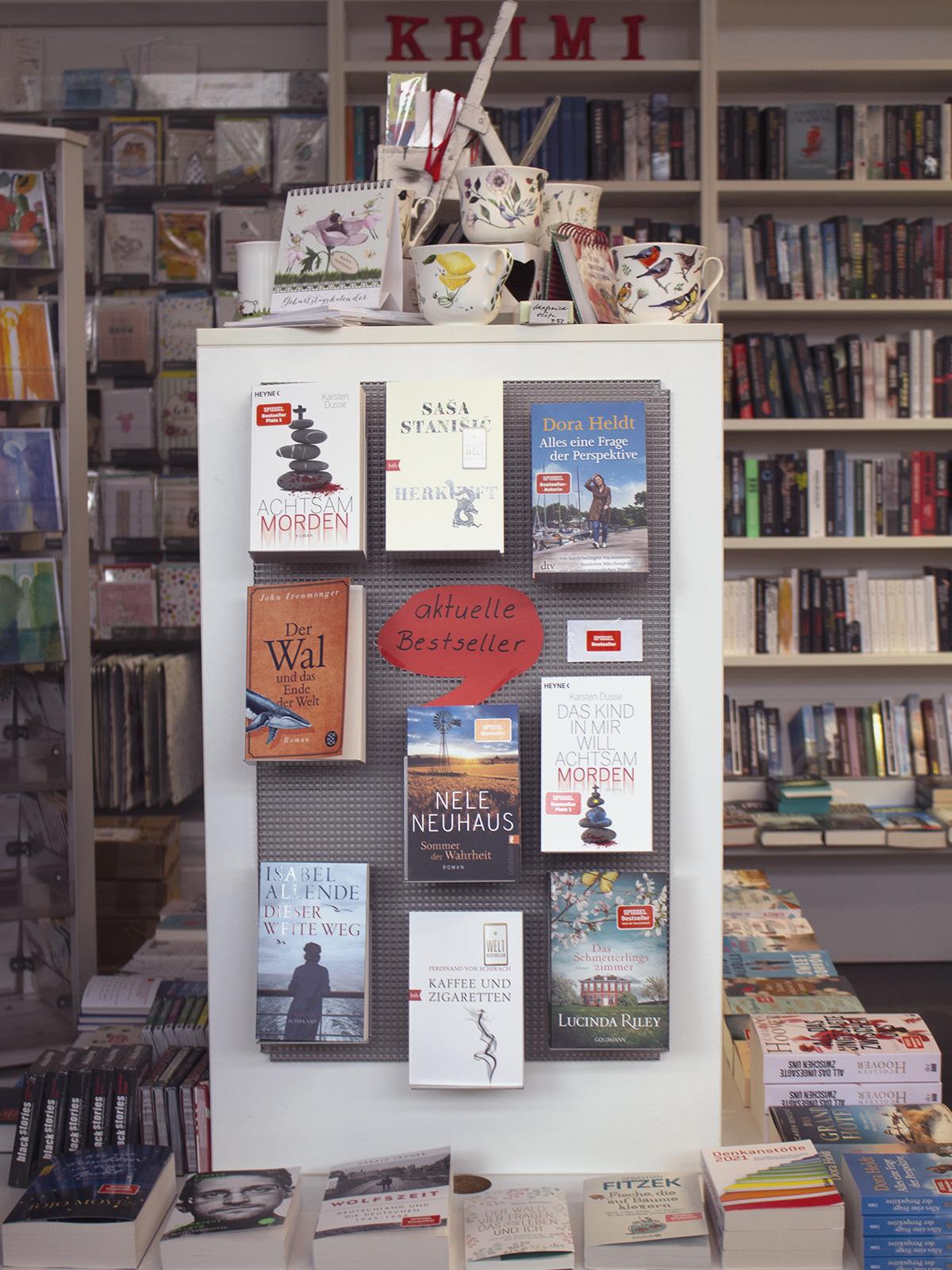 Man sieht eine Auswahl von neun Büchern aus der Bestseller-Liste frontal an einer Wand. Im Hintergrund ist eine Bücherwand, sowie Porzellan
