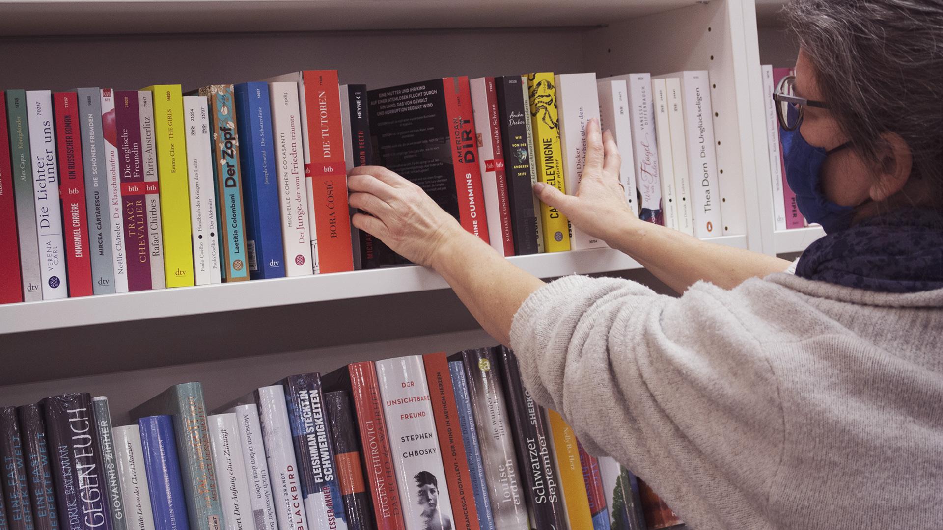 Man sieht die Arme einer Frau, die Bücher in einem Regal sortiert