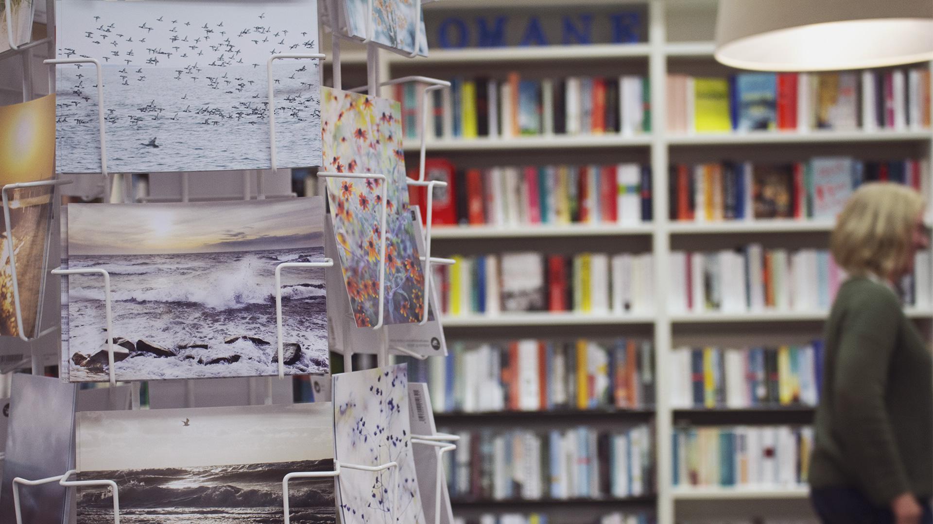 Links im Vordergrund sieht man einen Postkartenständer mit herbstlichen pastellfarbenen Postkarten und im Hintergrund eine Bücherwand