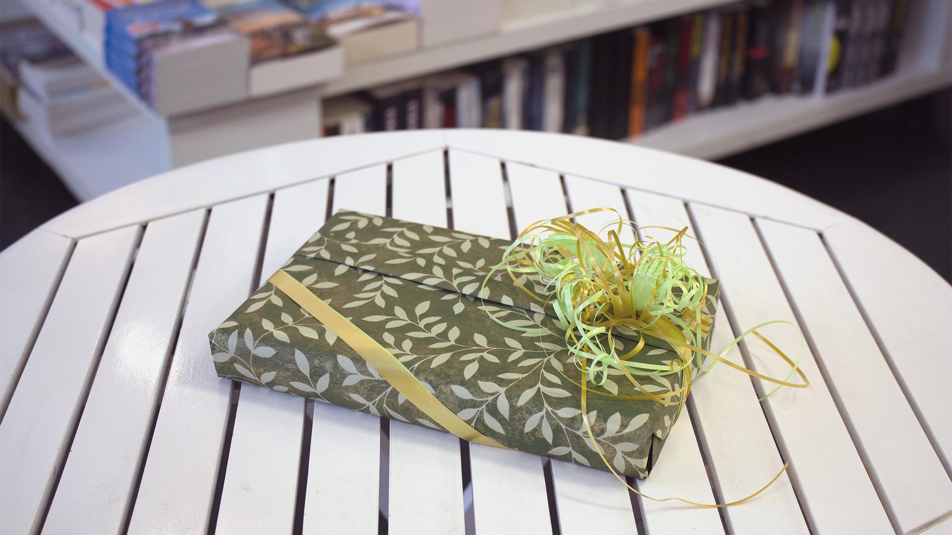 Ein als Geschenk verpacktes Buch mit grünem Papier und Schleife, das auf einem weißen Holztisch in der Buchhandlung liegt