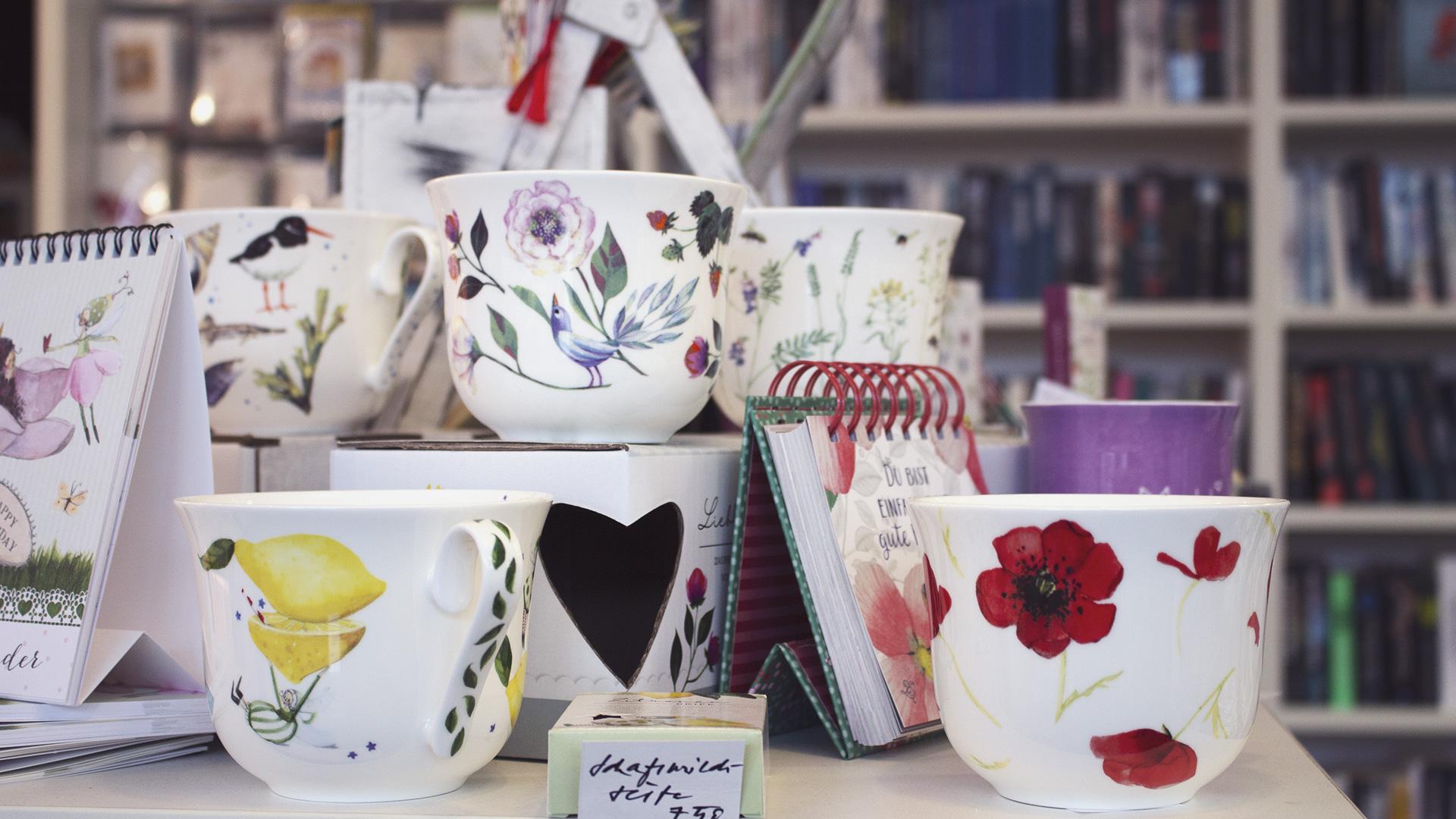feine Porzellantassen, die mit Blumenmotiven bemalt sind