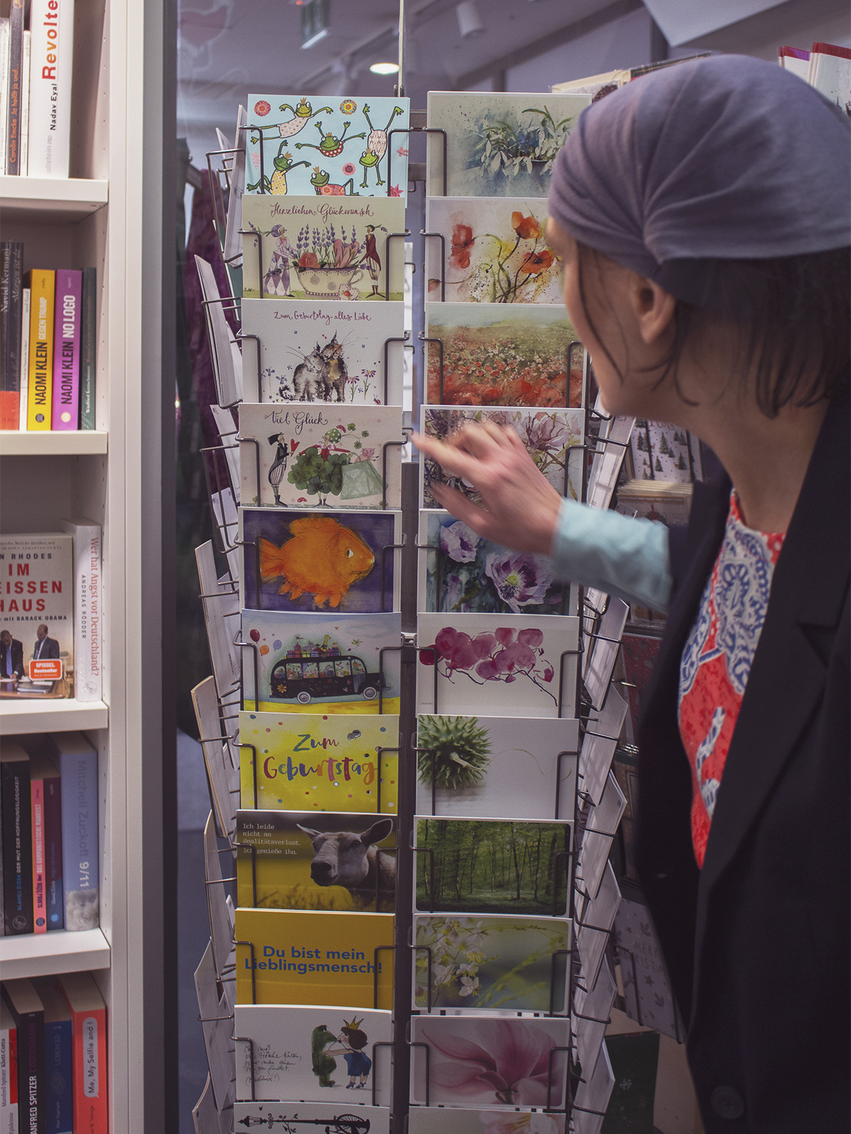 Eine Frau, die durch eine Auswahl an Herbstlichen Postkarten stöbert