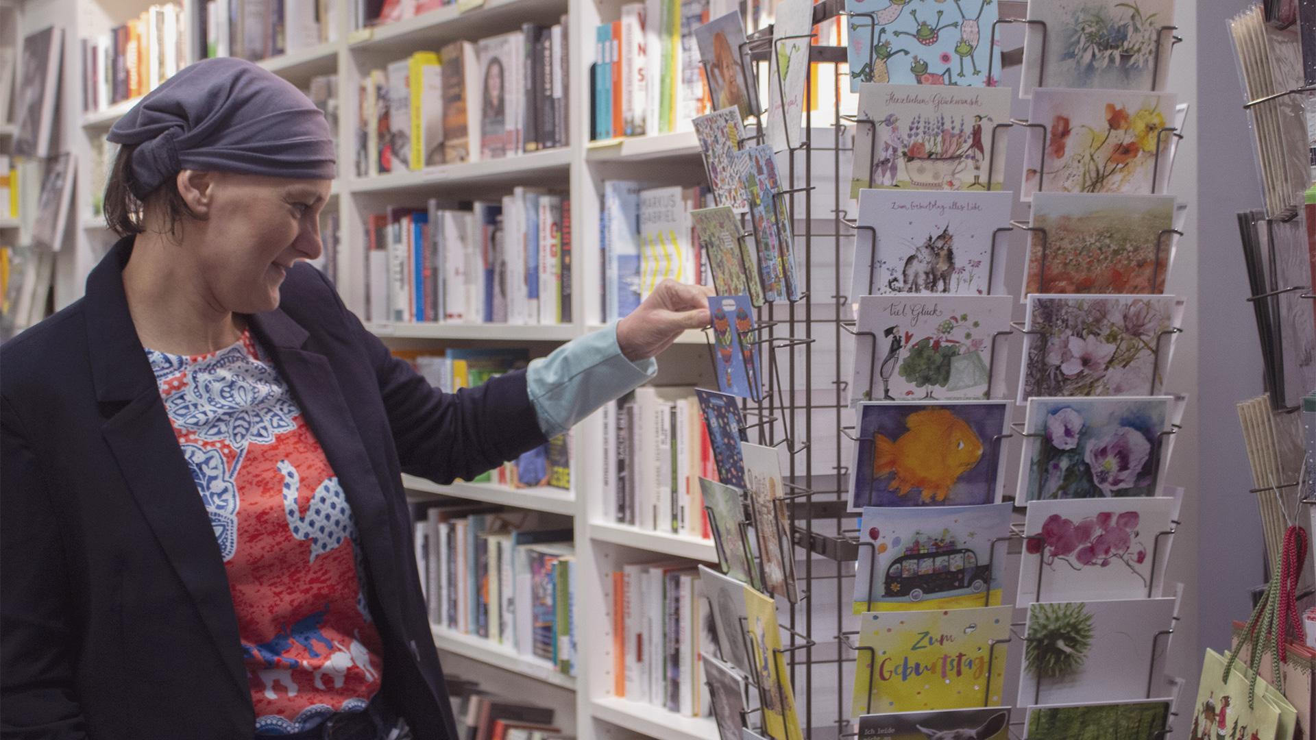 Postkarten mit Illustrationen und Sprüchen vor einer Bücherwand