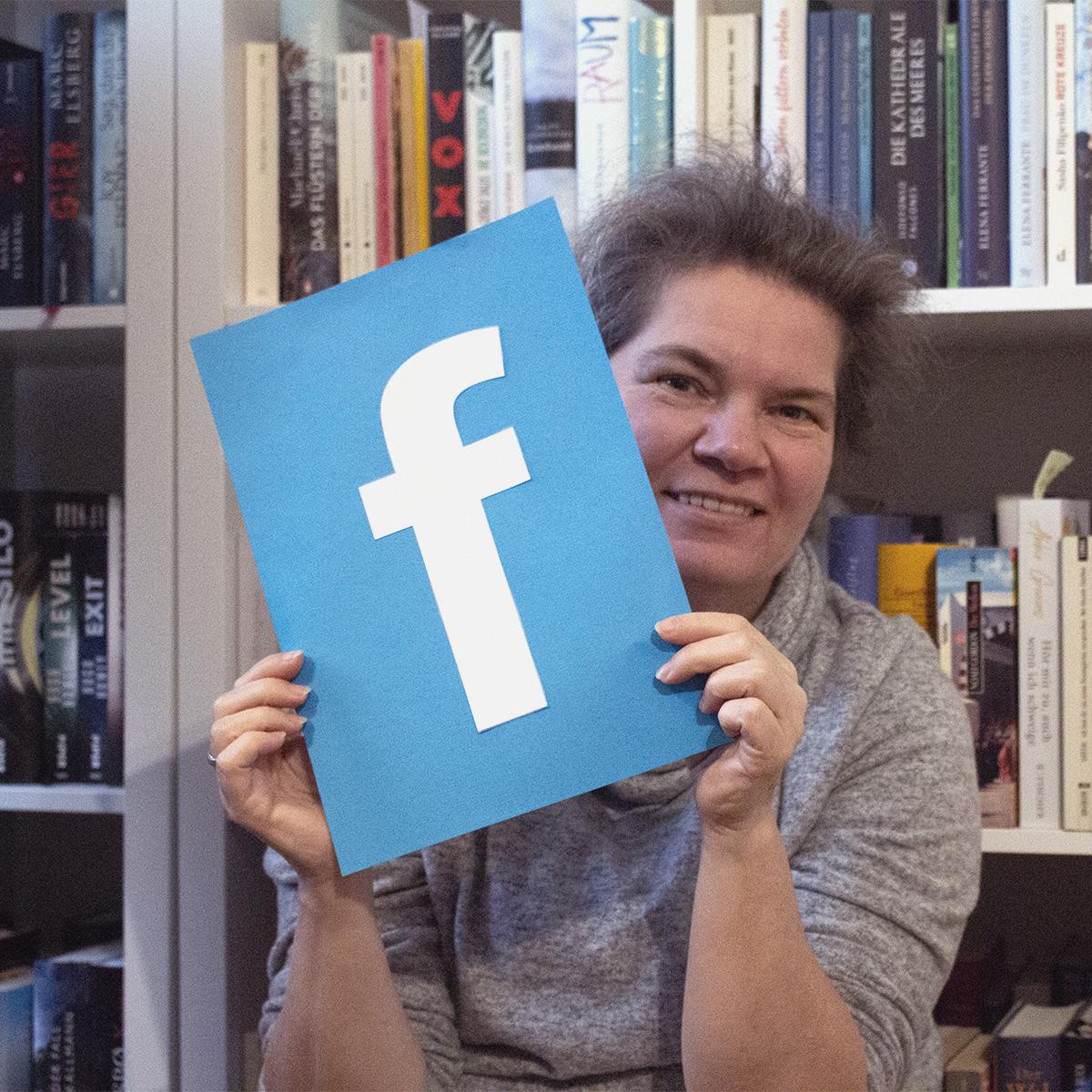 Mitarbeiterin der Buchhandlung am Rathaus Norderstedt hält ein Facebook-Poster hoch, um deren Facebookaccount zu bewerben